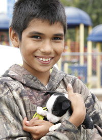 Boy holds his puppy at a Pets for Life clinic