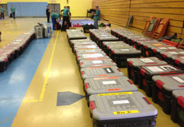 Containers of clinic supplies line the gym floor, ready to be loaded into the rig
