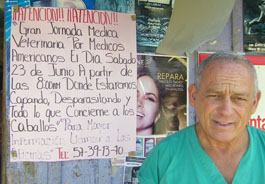 Dr. David Turoff posing near a flyer announcing the upcoming HSVMA-RAVS clinic in Guatemala